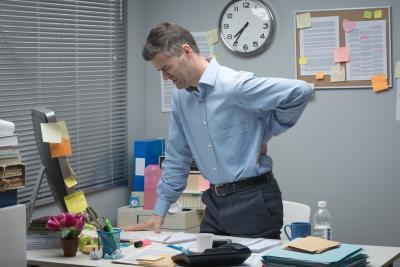 Dienstunfähigkeit kann jeden Beamten treffen: Beamter mit Rückenschmerzen