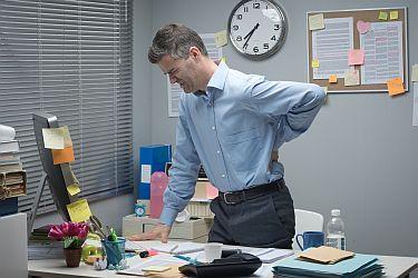 Mann im Büro hat Rückenschmerzen
